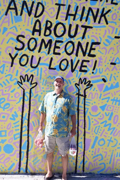 "L.J. Ganser standing in front of a Keith Haring mural that reads ""AND THINK ABOUT SOMEONE YOU LOVE!'"