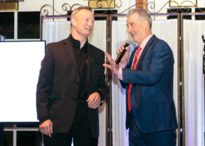 L.J Ganser, with Tony Award winning Bill Irwin, behind the microphone in a blue suit, red shirt and red patterned tie as auctioneer for the 2019 Wild Bird Flocktail Party